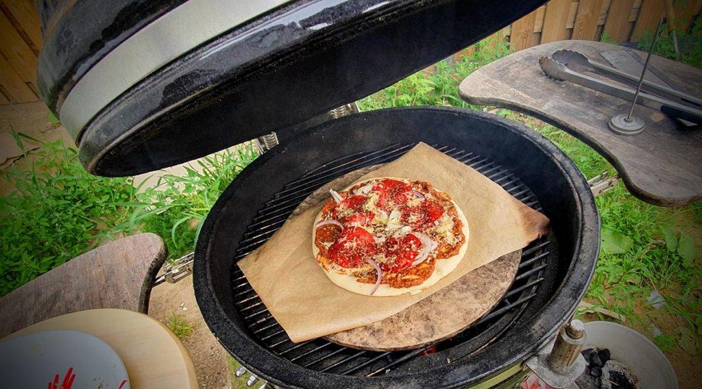 de pizza, met saus, en toppings op de gril