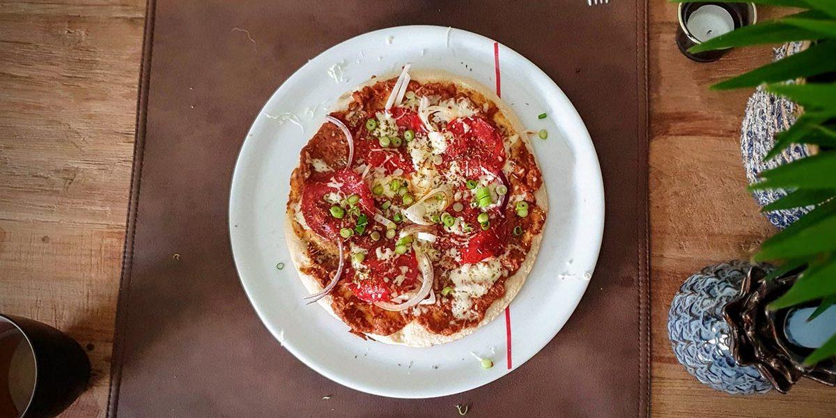 de pizza, met saus, klaar om te snijden en te eten